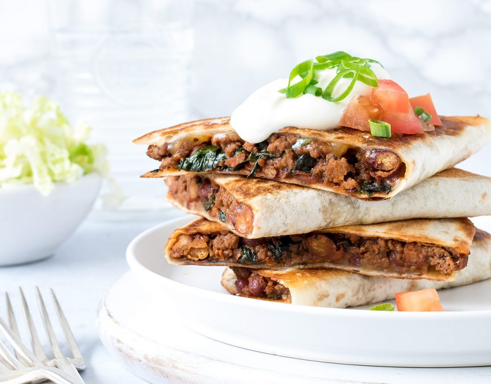 Beef quesadillas stacked up on a plate.