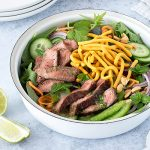 Large bowl of Thai beef salad with lime wedges and serving plates.