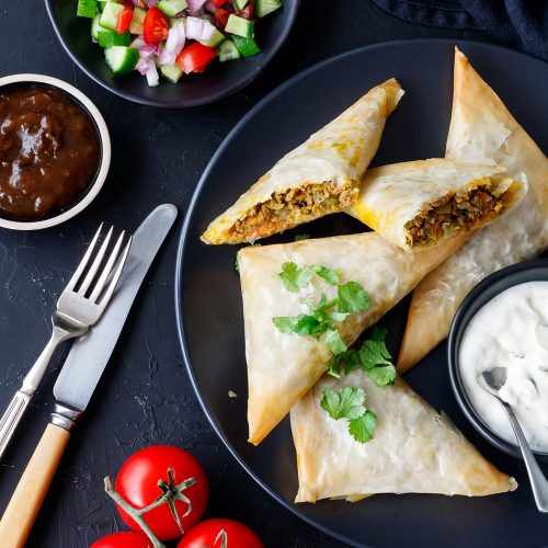 Lamb samosas on a plate with condiments.