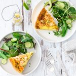 Two plates of leek and prawn quiche with salad and dressing.