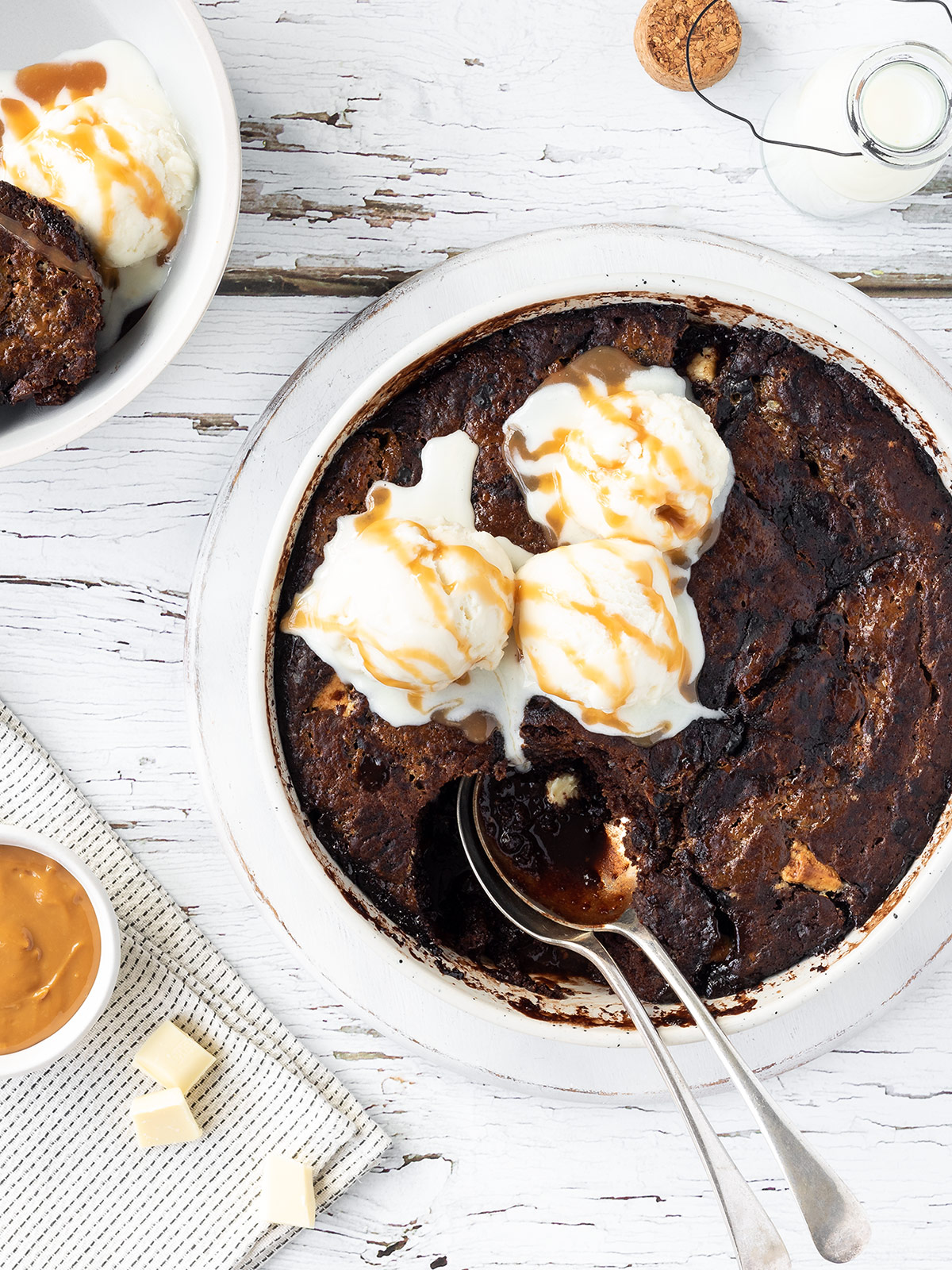 Chocolate caramel self saucing pudding with scoops of ice cream and caramel sauce on top.