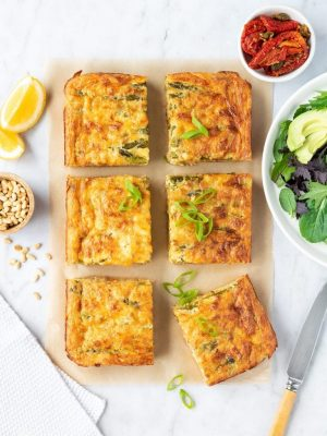 Tuna bake sliced into squares with salad ingredients on the side.