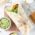 Vegetarian burrito on a board.