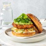 Salmon burger with salmon patty, slaw, avocado and rocket.