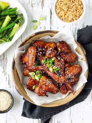 Bowl of sticky chicken wings with rice and greens.