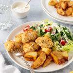 Lemon pepper fish bites with crispy roast potatoes and a fresh salad.