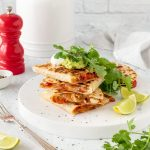 Chicken quesadillas with sour cream, avocado, rocket, coriander and lime.
