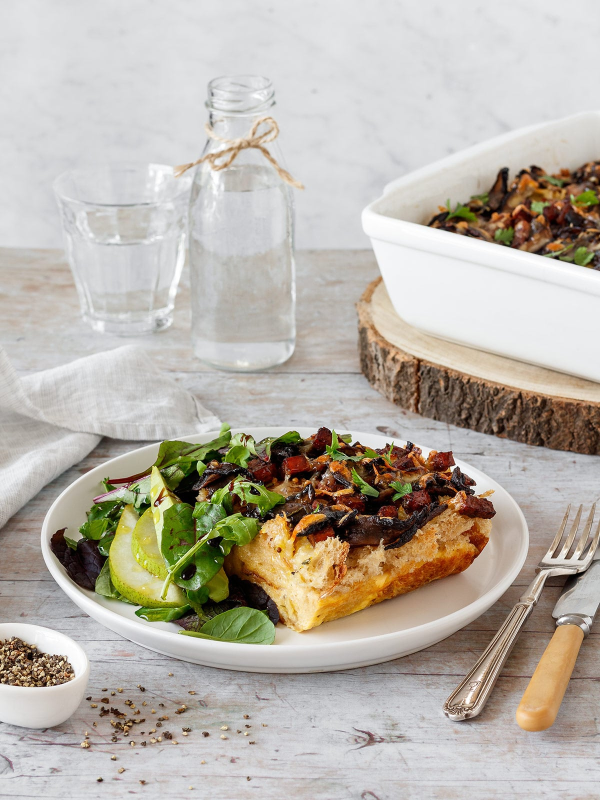 Savoury bread and butter pudding topped with mushrooms and chorizo, with a side of green salad.