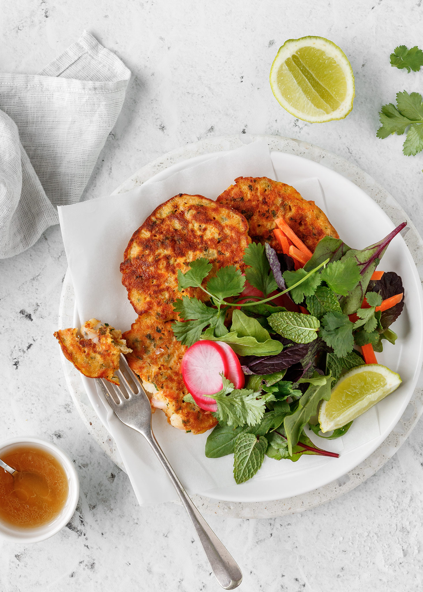 Thai prawn fritters with salad, fresh herbs, pickled radish and lime.