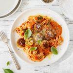 Spaghetti and veggie balls with creamy tomato sauce, parmesan and basil.