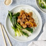 Asian-spiced orange pork with rice, greens and sesame seeds.