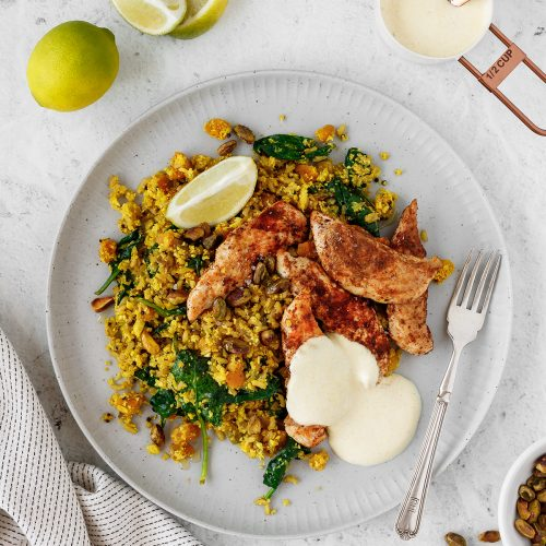 Middle Eastern spiced chicken and rice with turmeric yoghurt and lime wedges.