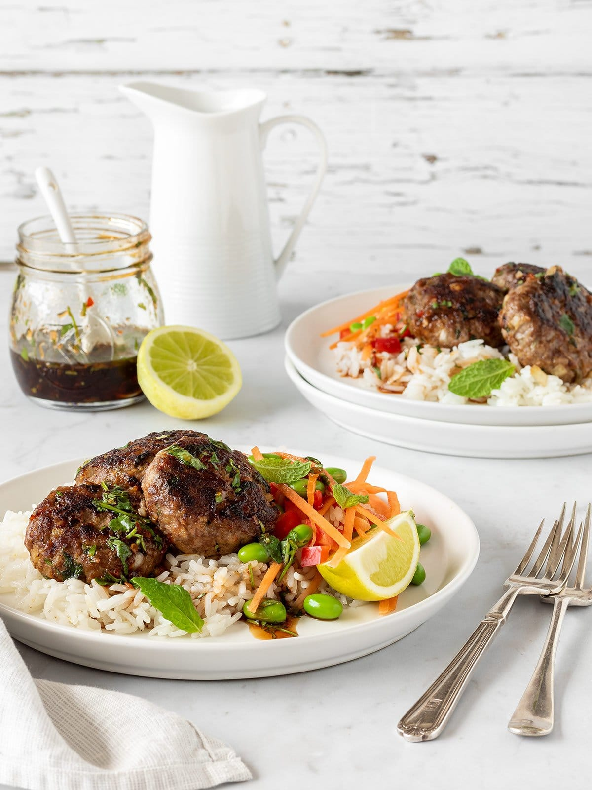Asian spiced lamb patties with jasmine rice, edamame, carrots, capsicum and a chilli lime dressing.
