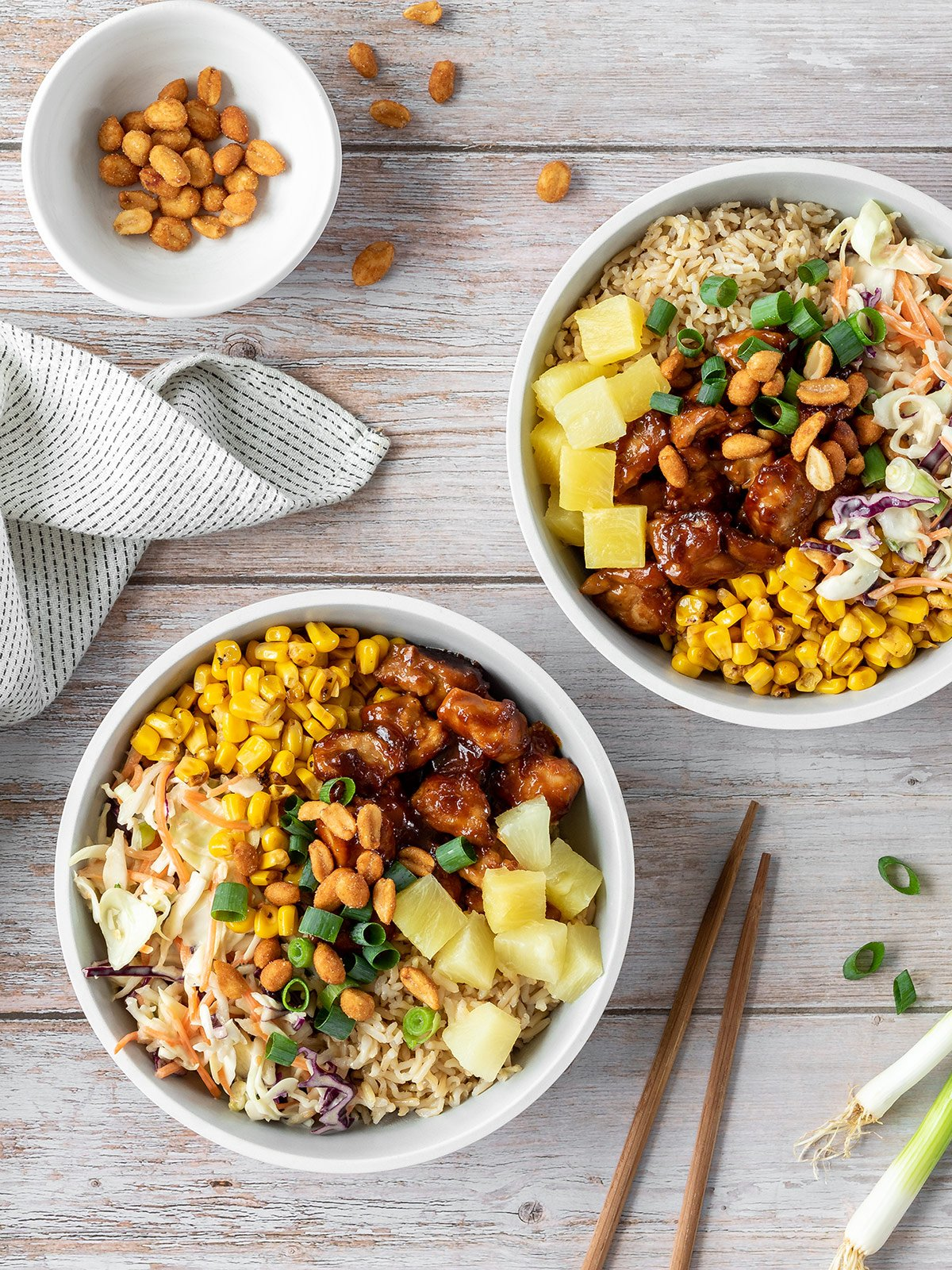 Chicken poke bowls with rice, Asian slaw, corn, pineapple, spring onions and honey roasted peanuts.