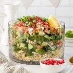 Layered salmon salad with pasta, rocket, prawns, avocado and pomegranate.