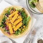 Fish finger wraps with greens, slaw, avocado and corn.