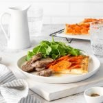 Roasted carrot tart with lamb sausages and salad greens.