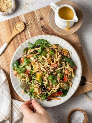 Café-style mango salmon salad with crispy noodles and soy toasted seeds.